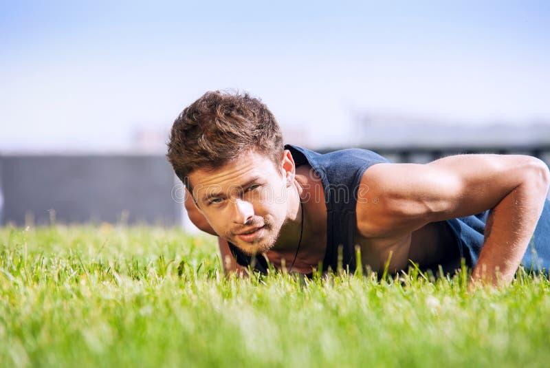 Υγιής νεαρός άνδρας που κάνει pushups υπαίθρια στοκ φωτογραφία