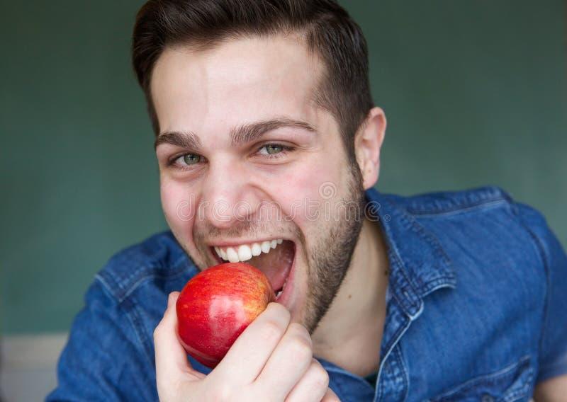 Υγιής νεαρός άνδρας που τρώει το μήλο στοκ φωτογραφίες