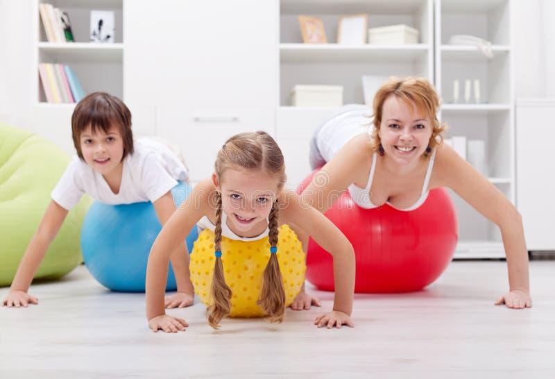 Υγιής οικογένεια που ασκεί με την ώθηση επάνω στις μεγάλες σφαίρες στοκ εικόνες