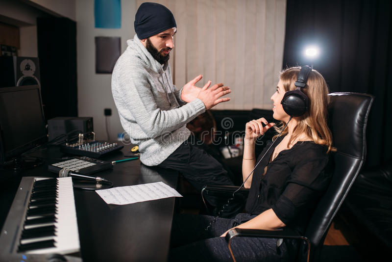 Υγιής παραγωγός με το θηλυκό τραγουδιστή στο στούντιο μουσικής στοκ εικόνες