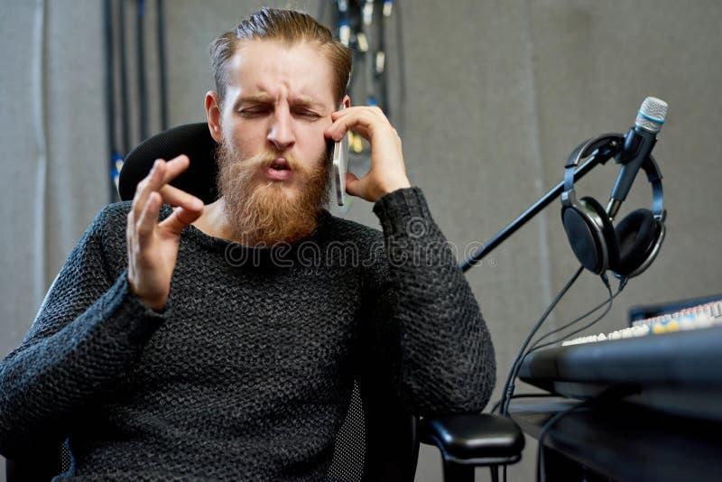 Υγιής παραγωγός που μιλά στο τηλέφωνο στο στούντιο στοκ εικόνες