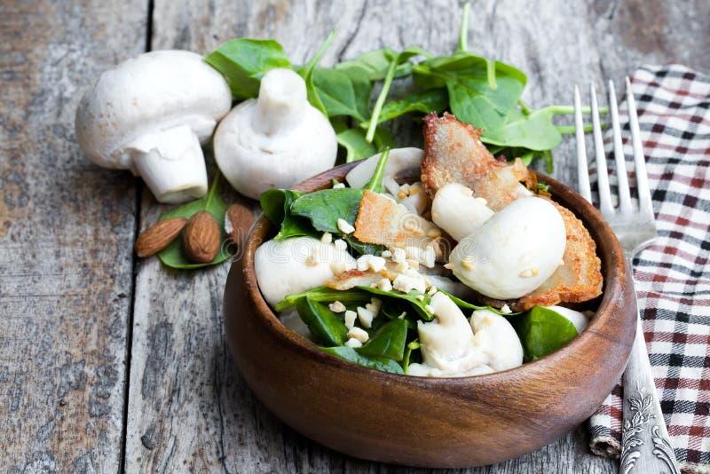 Υγιής σαλάτα μανιταριών με το σπανάκι και μπέϊκον στον ξύλινο πίνακα στοκ φωτογραφία με δικαίωμα ελεύθερης χρήσης