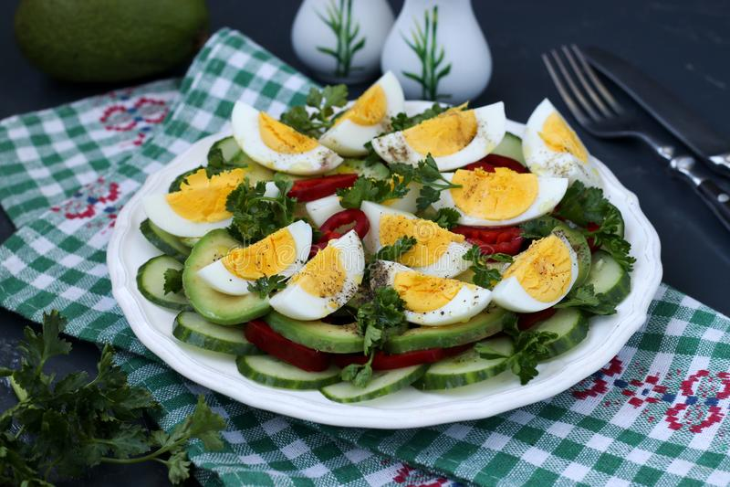 Υγιής σαλάτα του αβοκάντο, των αγγουριών, των αυγών και του γλυκού πιπεριού που βρίσκονται σε ένα πιάτο στοκ φωτογραφία