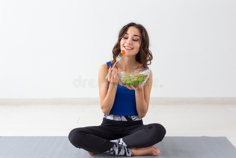 Υγιής τρόπος ζωής, άνθρωποι και αθλητική έννοια - γυναίκα γιόγκας με ένα κύπελλο της φυτικής σαλάτας στοκ φωτογραφία με δικαίωμα ελεύθερης χρήσης