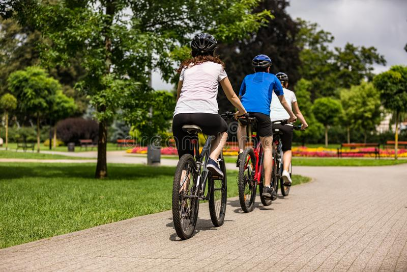 Υγιής τρόπος ζωής - άνθρωποι που οδηγούν τα ποδήλατα στο πάρκο πόλεων στοκ εικόνα
