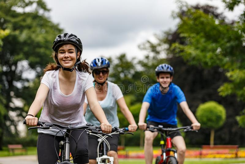 Υγιής τρόπος ζωής - άνθρωποι που οδηγούν τα ποδήλατα στο πάρκο πόλεων στοκ φωτογραφίες