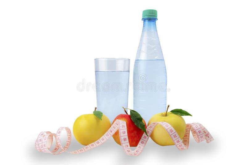 υγιής τρόπος ζωής έννοιας Τα μήλα, που μετρούν την ταινία, ποτήρι του νερού, μπουκάλι νερό σε ένα άσπρο υπόβαθρο, απομονώνουν στοκ φωτογραφίες με δικαίωμα ελεύθερης χρήσης