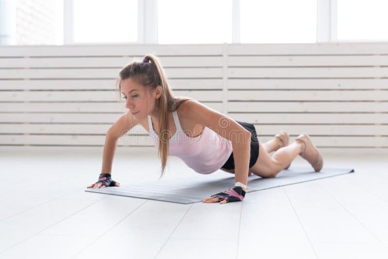 Υγιής τρόπος ζωής, αθλητισμός, έννοια ανθρώπων - μια νέα γυναίκα κάνει την ικανότητα στη γυμναστική ή το σπίτι Είναι πιέζοντας στοκ φωτογραφία με δικαίωμα ελεύθερης χρήσης