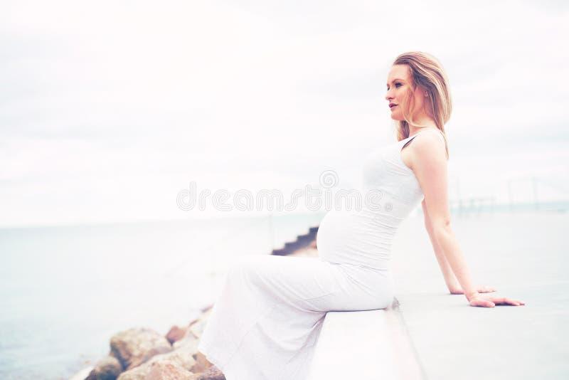 Υγιής χαλάρωση εγκύων γυναικών στην παραλία στοκ φωτογραφίες