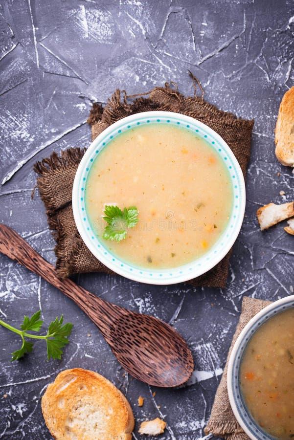 Υγιής χορτοφάγος σούπα μπιζελιών στο συγκεκριμένο υπόβαθρο στοκ εικόνα
