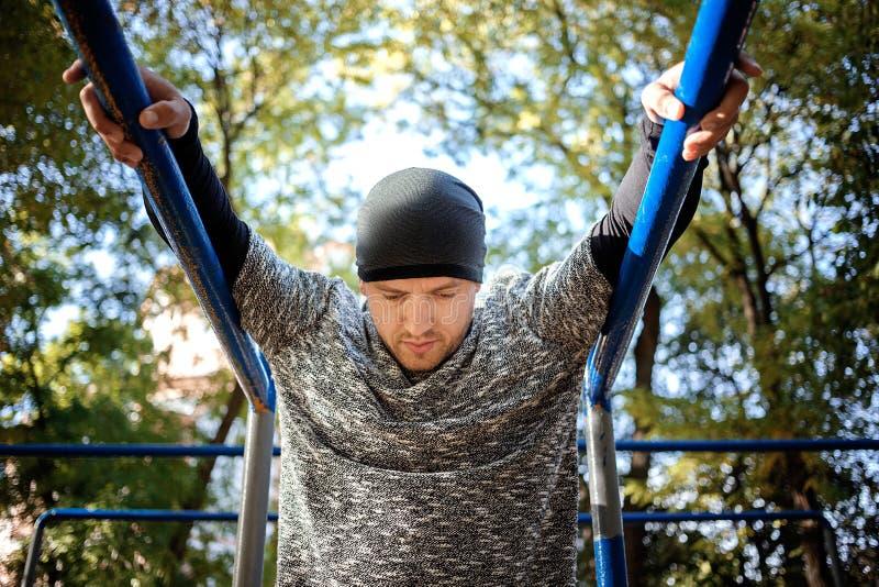 Υγιής όμορφος ενεργός άνδρας με το κατάλληλο μυϊκό σώμα που κάνει workout τις ασκήσεις υπαίθριος Αθλητισμός και έννοια ικανότητας στοκ φωτογραφία με δικαίωμα ελεύθερης χρήσης