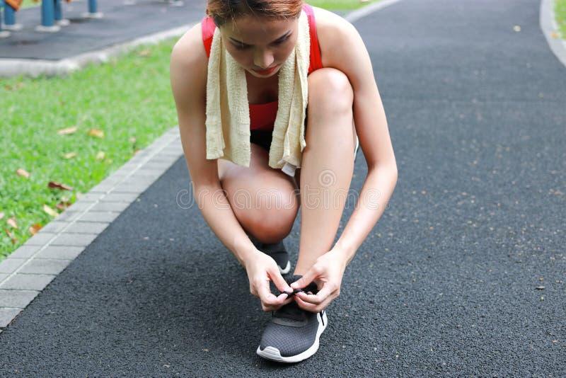 Υγιή ασιατικά δένοντας κορδόνια γυναικών στο τρέξιμο των παπουτσιών στην οδό Ικανότητα και έννοια Workout Wellness στοκ φωτογραφία με δικαίωμα ελεύθερης χρήσης