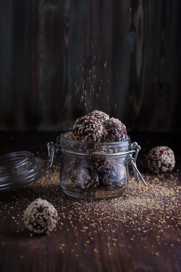 Υγιή δαγκώματα ενεργειακού granola με τα καρύδια, ημερομηνίες, μέλι και σουσάμι σε ένα βάζο γυαλιού σε ένα σκοτεινό ξύλινο υπόβαθ στοκ φωτογραφία με δικαίωμα ελεύθερης χρήσης