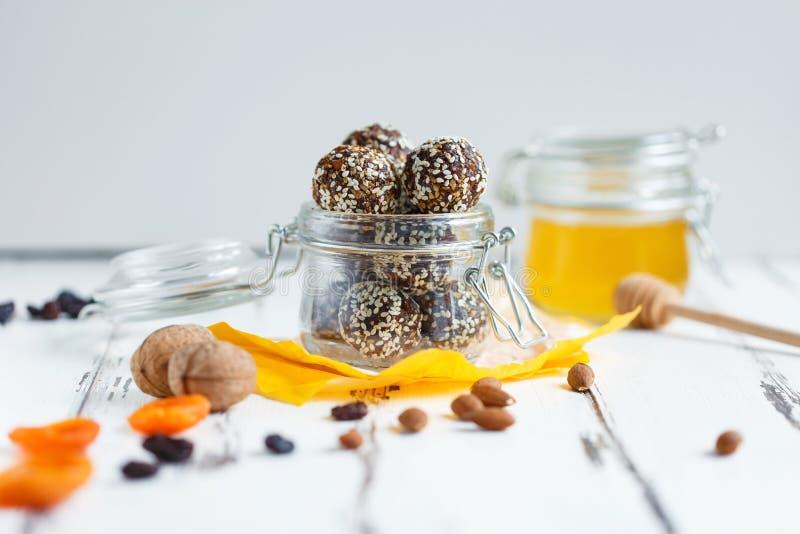 Υγιή δαγκώματα ενεργειακού granola με τα καρύδια, ημερομηνίες, μέλι και σουσάμι σε ένα βάζο γυαλιού σε έναν άσπρο πίνακα στοκ εικόνα