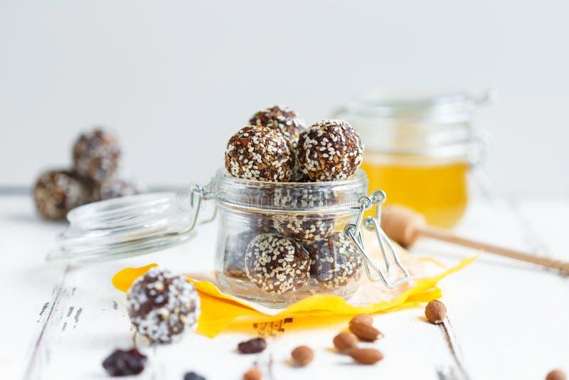 Υγιή δαγκώματα ενεργειακού granola με τα καρύδια, ημερομηνίες, μέλι και σουσάμι σε ένα βάζο γυαλιού σε έναν άσπρο πίνακα στοκ φωτογραφία με δικαίωμα ελεύθερης χρήσης