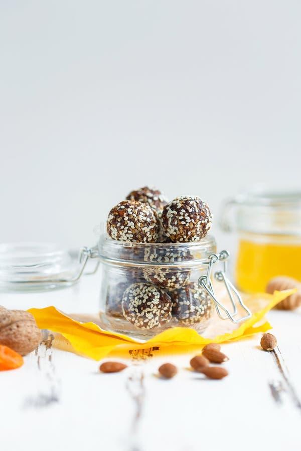 Υγιή δαγκώματα ενεργειακού granola με τα καρύδια, ημερομηνίες, μέλι και σουσάμι σε ένα βάζο γυαλιού σε έναν άσπρο πίνακα στοκ φωτογραφίες