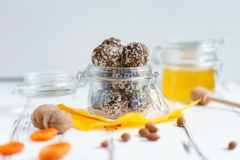 Υγιή δαγκώματα ενεργειακού granola με τα καρύδια, ημερομηνίες, μέλι και σουσάμι σε ένα βάζο γυαλιού σε έναν άσπρο πίνακα στοκ εικόνες