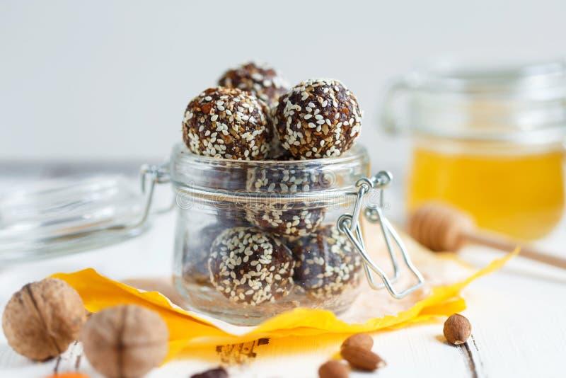 Υγιή δαγκώματα ενεργειακού granola με τα καρύδια, ημερομηνίες, μέλι και σουσάμι σε ένα βάζο γυαλιού σε έναν άσπρο πίνακα στοκ εικόνα με δικαίωμα ελεύθερης χρήσης
