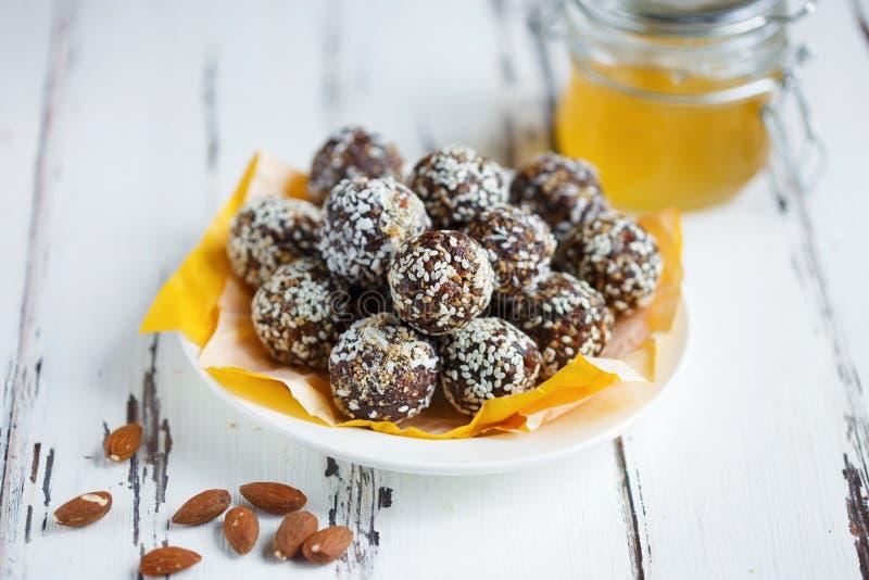 Υγιή ενεργειακά οργανικά δαγκώματα με τα καρύδια, ημερομηνίες, μέλι και σουσάμι σε ένα πιάτο σε ένα ελαφρύ ξύλινο υπόβαθρο στοκ εικόνες