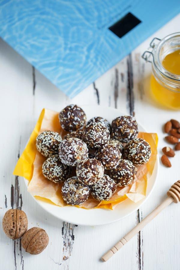 Υγιή ενεργειακά οργανικά δαγκώματα με τα καρύδια, ημερομηνίες, μέλι και σουσάμι σε ένα πιάτο σε ένα ελαφρύ ξύλινο υπόβαθρο στοκ φωτογραφίες με δικαίωμα ελεύθερης χρήσης