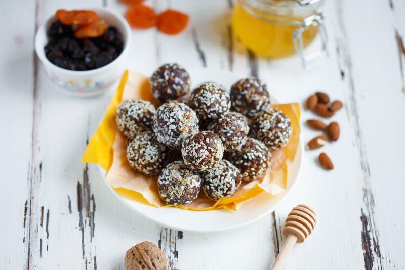 Υγιή ενεργειακά οργανικά δαγκώματα με τα καρύδια, ημερομηνίες, μέλι και σουσάμι σε ένα πιάτο σε ένα ελαφρύ ξύλινο υπόβαθρο στοκ φωτογραφία