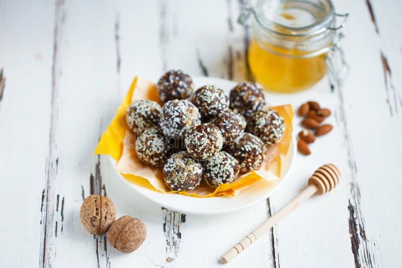 Υγιή ενεργειακά οργανικά δαγκώματα με τα καρύδια, ημερομηνίες, μέλι και σουσάμι σε ένα πιάτο σε ένα ελαφρύ ξύλινο υπόβαθρο στοκ εικόνα