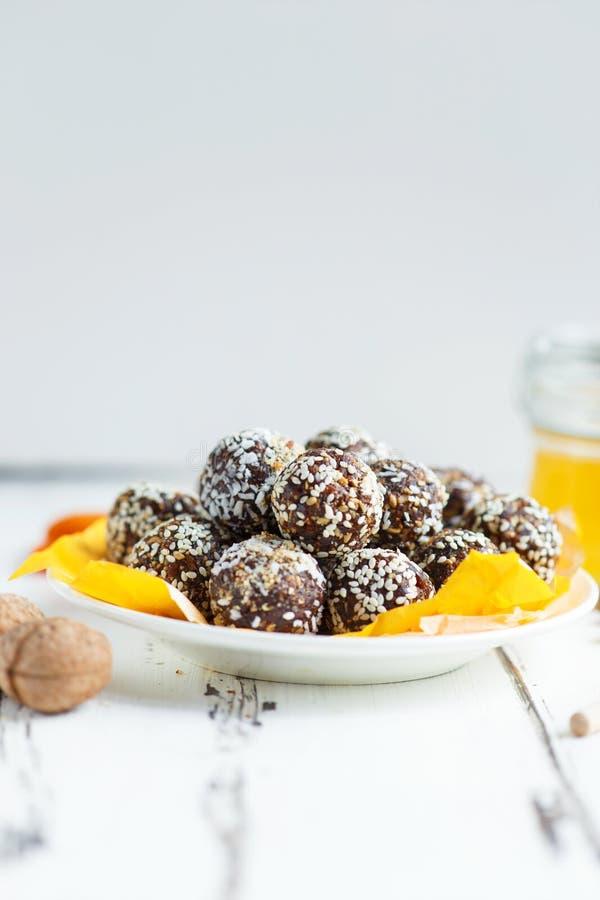 Υγιή ενεργειακά οργανικά δαγκώματα με τα καρύδια, ημερομηνίες, μέλι και σουσάμι σε ένα πιάτο σε ένα ελαφρύ ξύλινο υπόβαθρο στοκ εικόνες με δικαίωμα ελεύθερης χρήσης