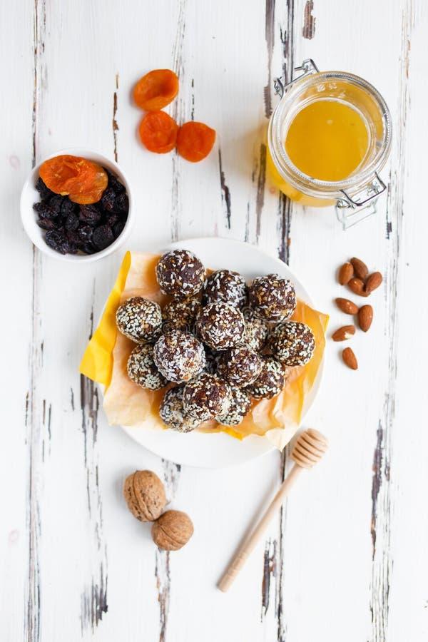 Υγιή ενεργειακά οργανικά δαγκώματα με τα καρύδια, ημερομηνίες, μέλι και σουσάμι σε ένα πιάτο σε ένα ελαφρύ ξύλινο υπόβαθρο στοκ φωτογραφίες