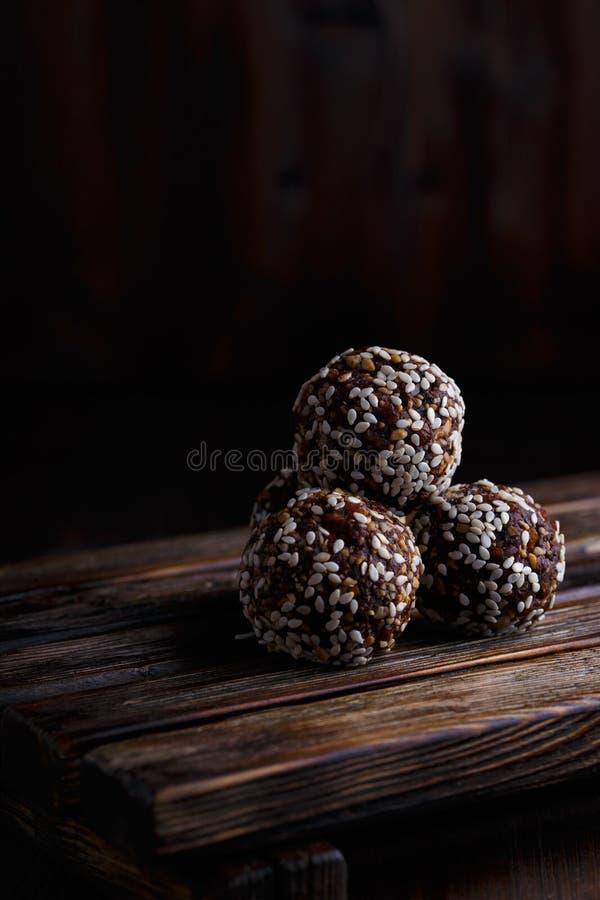 Υγιή ενεργειακά οργανικά χορτοφάγα δαγκώματα με τα καρύδια, ημερομηνίες, μέλι και σουσάμι σε ένα σκοτεινό ξύλινο υπόβαθρο στοκ φωτογραφία με δικαίωμα ελεύθερης χρήσης