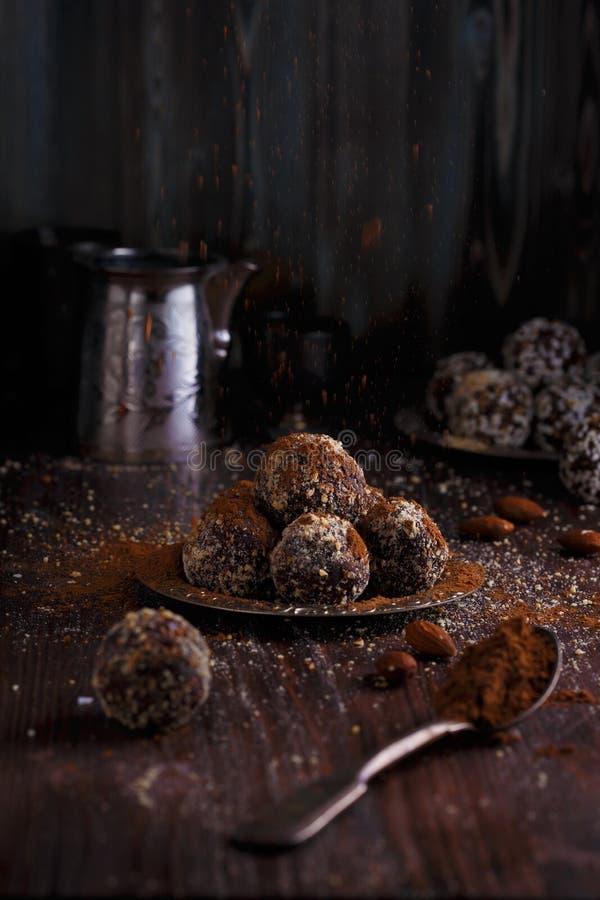 Υγιή ενεργειακά οργανικά χορτοφάγα δαγκώματα με τα καρύδια, ημερομηνίες, μέλι, κακάο και σουσάμι σε ένα σκοτεινό ξύλινο υπόβαθρο στοκ φωτογραφία