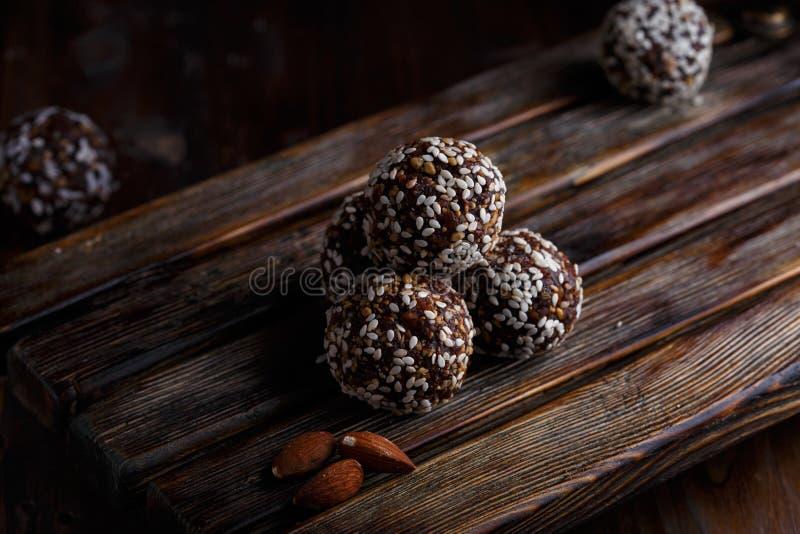 Υγιή ενεργειακά οργανικά χορτοφάγα δαγκώματα με τα καρύδια, ημερομηνίες, μέλι και σουσάμι σε ένα σκοτεινό ξύλινο υπόβαθρο στοκ εικόνες