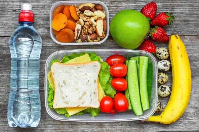 Υγιή καλαθάκια με φαγητό με το σάντουιτς, τα αυγά και τα φρέσκα λαχανικά, το μπουκάλι νερό, τα καρύδια και τα φρούτα στοκ εικόνες