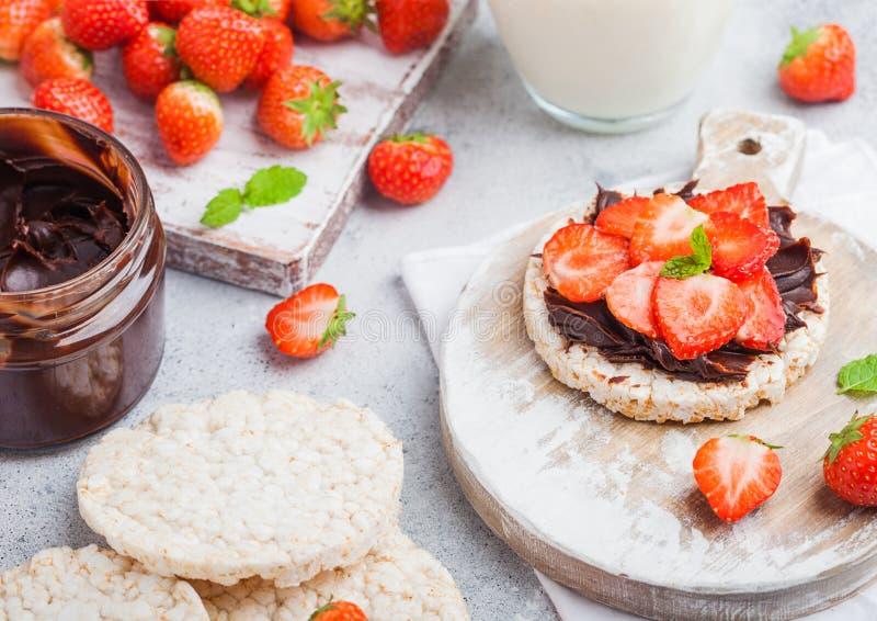 Υγιή οργανικά κέικ ρυζιού με τις βουτύρου και φρέσκες φράουλες σοκολάτας στον ξύλινους πίνακα και το ποτήρι του γάλακτος στην ελα στοκ φωτογραφίες