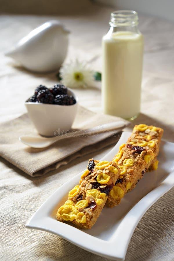 Υγιή οργανικά μπισκότα με το μπουκάλι μούρων του ντεκόρ γάλακτος και πινάκων στο τραπεζομάντιλο λινού στοκ εικόνα με δικαίωμα ελεύθερης χρήσης