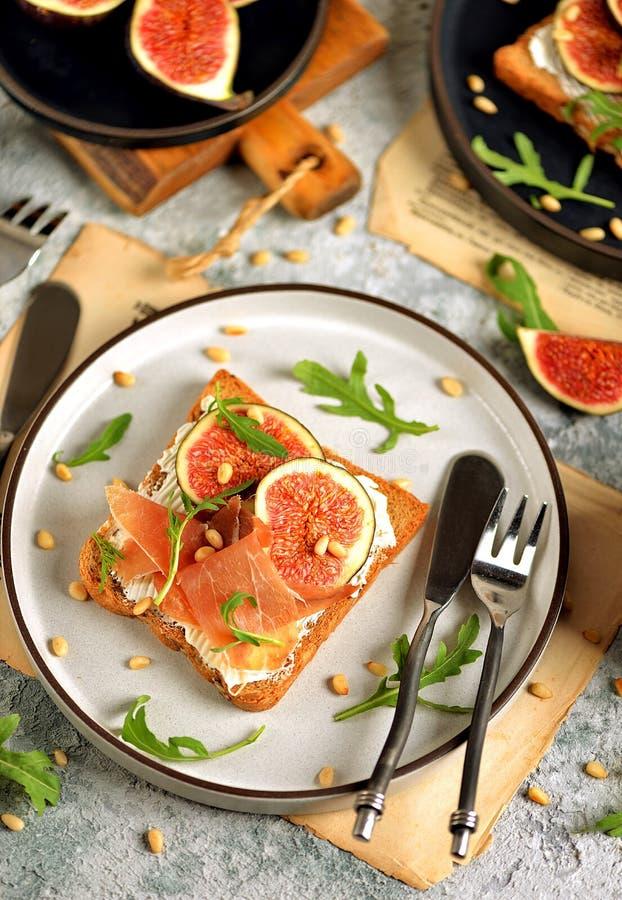 Υγιή σάντουιτς από το ψωμί σίκαλης με το μαλακό τυρί, jamon, τα σύκα, τα καρύδια arugula και πεύκων στοκ εικόνες