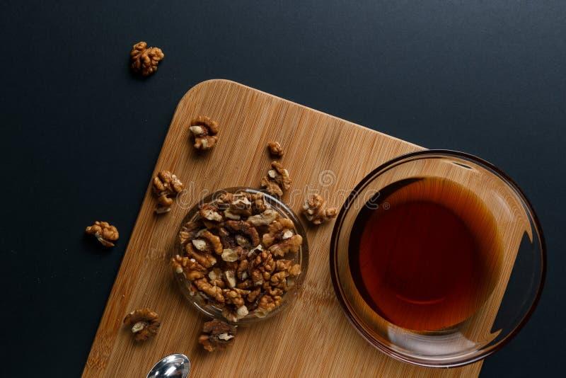 Υγιή συστατικά προγευμάτων: μέλι, ξύλα καρυδιάς σε ένα σκοτεινό υπόβαθρο στοκ φωτογραφίες