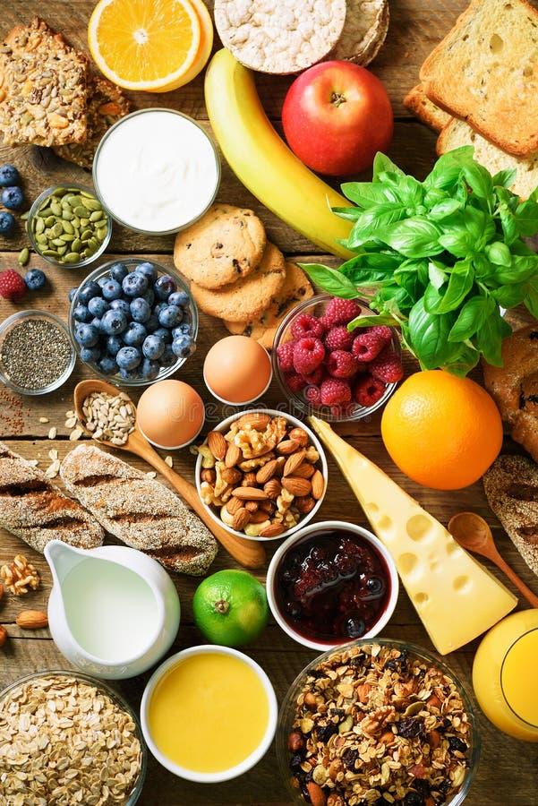 Υγιή συστατικά προγευμάτων, πλαίσιο τροφίμων Granola, αυγό, καρύδια, φρούτα, μούρα, φρυγανιά, γάλα, γιαούρτι, χυμός από πορτοκάλι στοκ εικόνα