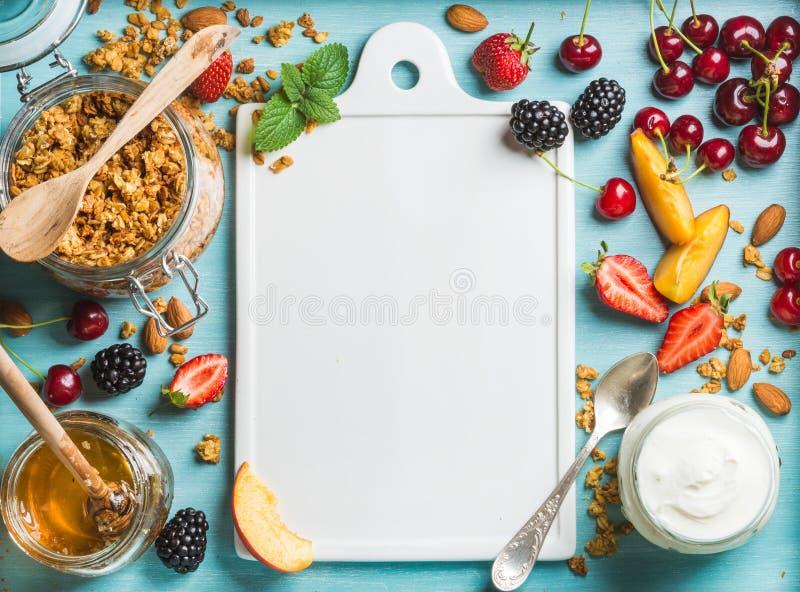 Υγιή συστατικά προγευμάτων Granola βρωμών στο ανοικτό βάζο, το γιαούρτι, τα φρούτα, τα μούρα, το μέλι και τη μέντα γυαλιού στο μπ στοκ εικόνες