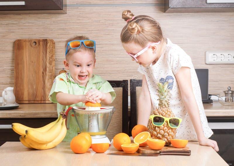 Υγιή τρόφιμα: ένα κορίτσι και ένα αγόρι κάνουν το φρέσκο χυμό από πορτοκάλι στοκ φωτογραφία με δικαίωμα ελεύθερης χρήσης