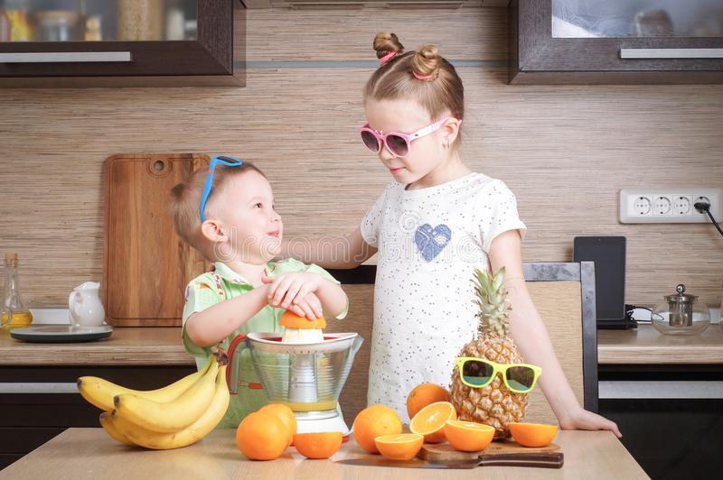 Υγιή τρόφιμα: ένα κορίτσι και ένα αγόρι κάνουν το φρέσκο χυμό από πορτοκάλι στοκ εικόνα
