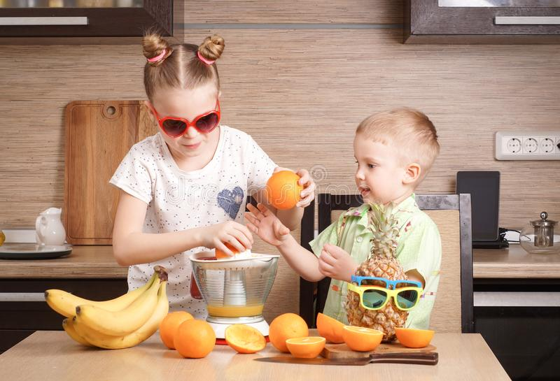 Υγιή τρόφιμα: ένα κορίτσι και ένα αγόρι κάνουν το φρέσκο χυμό από πορτοκάλι στοκ φωτογραφίες