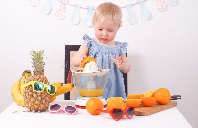 Υγιή τρόφιμα: Ένα μικρό κορίτσι κάνει το φρέσκο χυμό από πορτοκάλι στοκ εικόνες με δικαίωμα ελεύθερης χρήσης