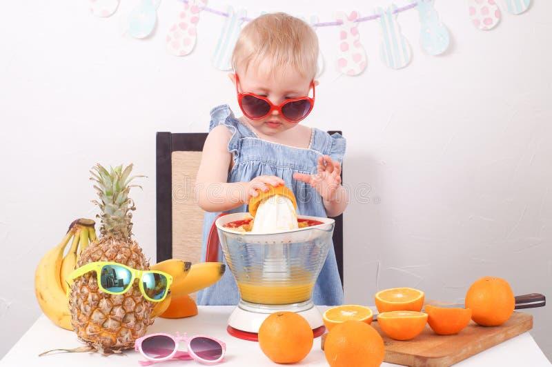 Υγιή τρόφιμα: Ένα μικρό κορίτσι κάνει το φρέσκο χυμό από πορτοκάλι στοκ φωτογραφίες με δικαίωμα ελεύθερης χρήσης