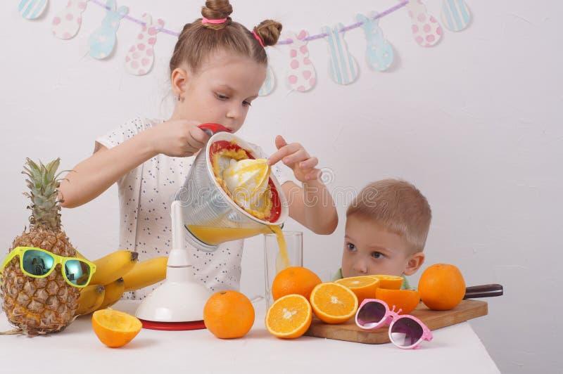 Υγιή τρόφιμα για τα παιδιά: Ένα κορίτσι και ένα αγόρι κάνουν το χυμό από πορτοκάλι στοκ εικόνα