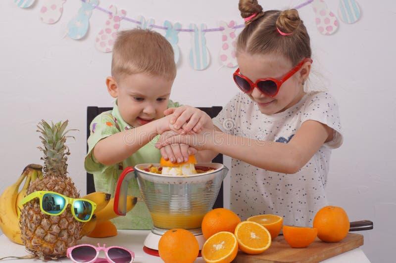 Υγιή τρόφιμα για τα παιδιά: Ένα κορίτσι και ένα αγόρι κάνουν το χυμό από πορτοκάλι στοκ φωτογραφία