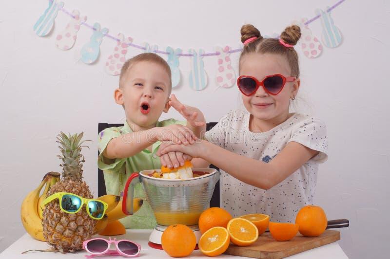 Υγιή τρόφιμα για τα παιδιά: Ένα κορίτσι και ένα αγόρι κάνουν το χυμό από πορτοκάλι στοκ εικόνες με δικαίωμα ελεύθερης χρήσης
