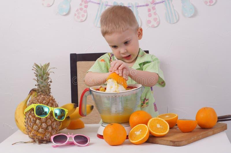 Υγιή τρόφιμα για τα παιδιά: Ένα κορίτσι και ένα αγόρι κάνουν το χυμό από πορτοκάλι στοκ φωτογραφίες