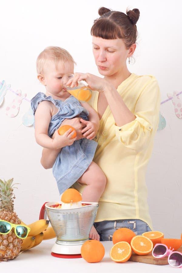 Υγιή τρόφιμα για τα παιδιά: Το Mom θεραπεύει την κόρη της με το φρέσκο χυμό από πορτοκάλι στοκ φωτογραφίες με δικαίωμα ελεύθερης χρήσης