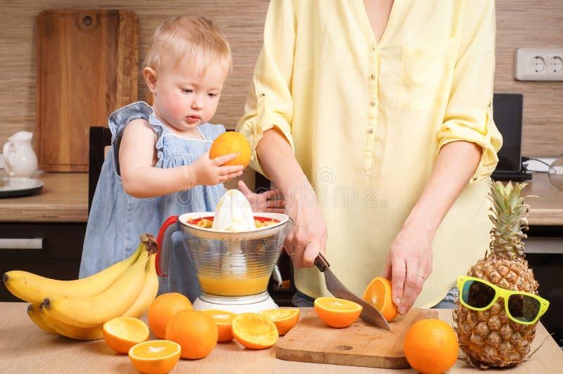 Υγιή τρόφιμα για τα παιδιά: Το Mom και η κόρη κάνουν το φρέσκο χυμό από πορτοκάλι στοκ φωτογραφίες
