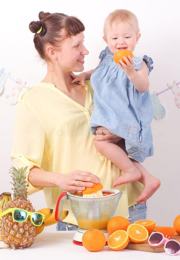 Υγιή τρόφιμα για τα παιδιά: Το Mom και η κόρη κάνουν το φρέσκο χυμό από πορτοκάλι στοκ φωτογραφία με δικαίωμα ελεύθερης χρήσης